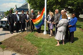 Councillors, other digitiaries and community members raise the Rainbow Flag at the City of Markham civic centre.